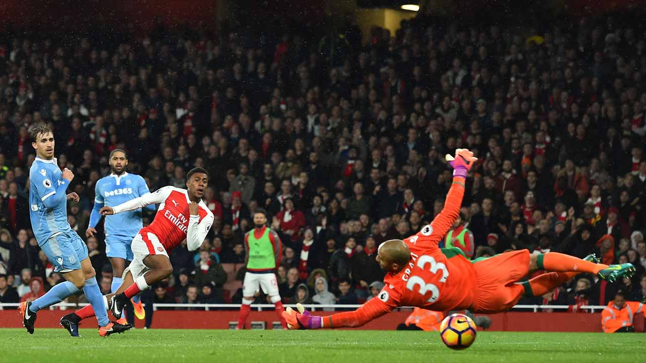 Arsenal's Nigerian striker Alex Iwobi (3L) shoots and scores past Stoke City's English goalkeeper Lee Grant during the English Premier League football match between Arsenal and Stoke City at the Emirates Stadium in London on December 10, 2016. Glyn KIRK / AFP