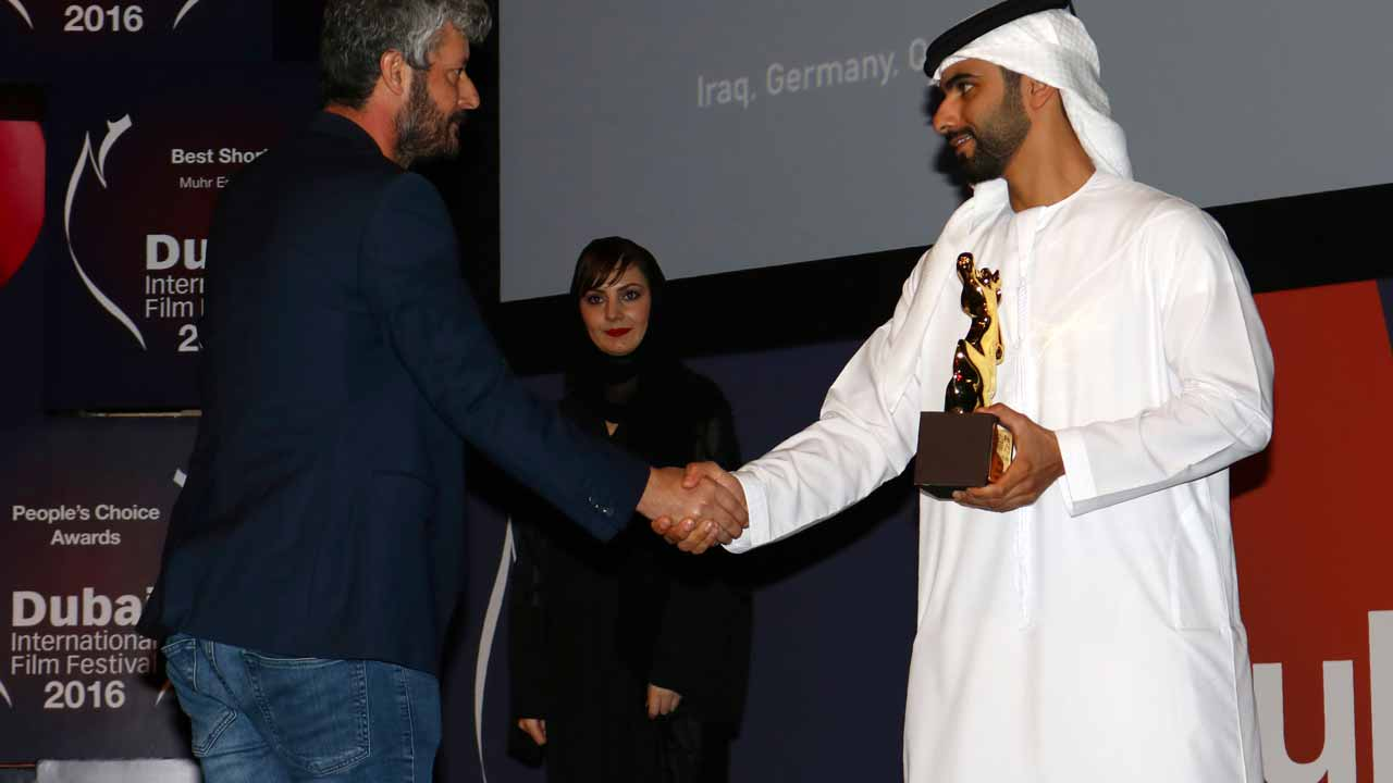 "Kurdistan's director and actor, Hussein Hassan receives the ""Best Muhr fiction feature"" award from Sheikh Mansoor bin Mohammed bin Rashid al-Maktoum (R) during the closing ceremony of the 13th Dubai Film festival on December 14, 2016 at Madinat Jumeirah resort in Dubai. Hassan was awarded for his movie titled Reseba (The dark wind). NEZAR BALOUT / AFP"
