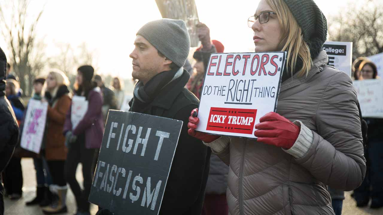 Activists hold anti-Trump signs during a demonstration hosted by #TURNOUT at the Sylvan Theatre near the Washington Monument in Washington, DC, December 17, 2016. PHOTO: ZACH GIBSON / AFP