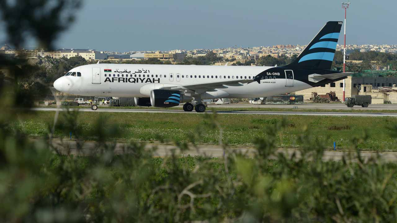 "A picture taken on December 23, 2016 shows a Malta armed forces truck sitting by the Afriqiyah Airways A320 after it landed in Valletta, Malta, following its hijacking from Libya. A man who said he was armed with a grenade hijacked a Libyan plane which landed on Malta Friday with 118 people on board, Malta's prime minister and government sources on the Mediterranean island said. After more than an hour on the tarmac, the plane's door opened and a first group of women and children were seen descending a mobile staircase. ""First group of passengers, consisting of women and children, being released now,"" Prime Minister Joseph Muscat said on Twitter, adding in a later tweet that 50 passengers in all were being let off the plane. PHOTO: Matthew Mirabelli / AFP"