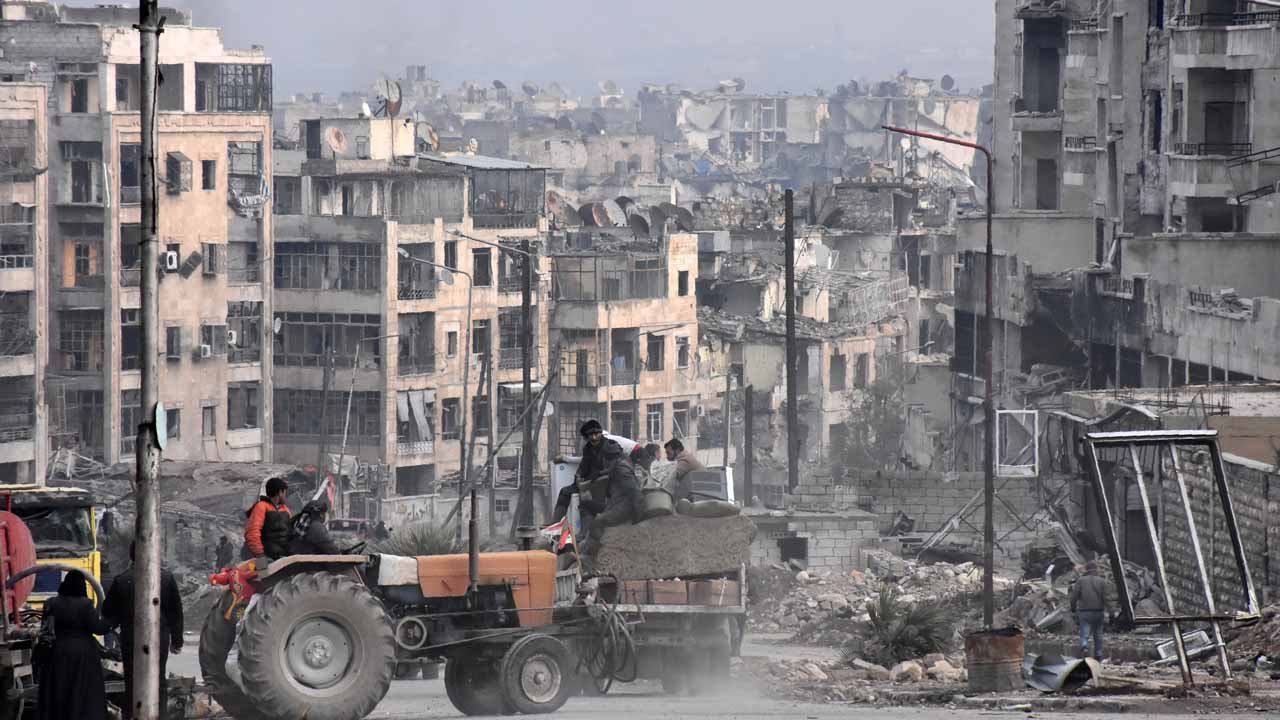 Syrians use a tractor to collect belongings in the former rebel-held Zebdiye district in the northern Syrian city of Aleppo on December 23, 2016 after Syrian government forces retook control of the whole embattled city. Syrian troops cemented their hold on Aleppo after retaking full control of the city, as residents anxious to return to their homes moved through its ruined streets. PHOTO: George OURFALIAN / AFP