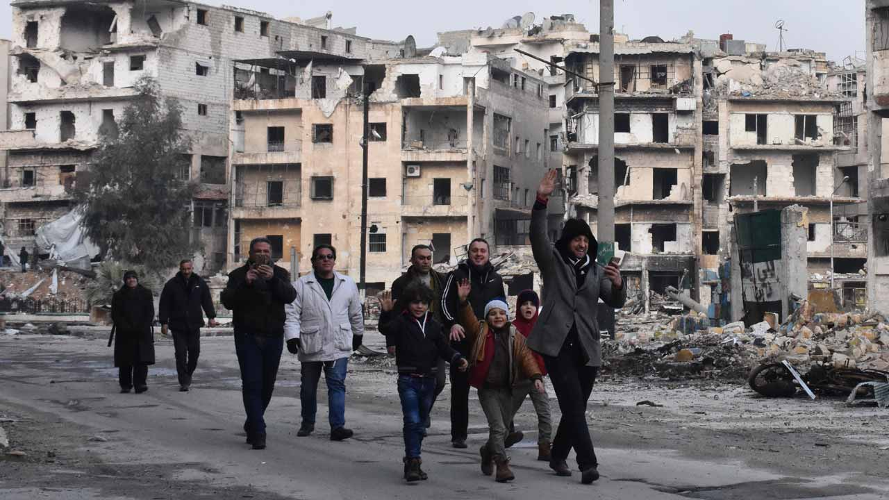 Syrians walk through the former rebel-held Salaheddin district in the northern Syrian city of Aleppo on December 23, 2016 after Syrian government forces retook control of the whole embattled city. Syrian troops cemented their hold on Aleppo after retaking full control of the city, as residents anxious to return to their homes moved through its ruined streets. PHOTO: George OURFALIAN / AFP