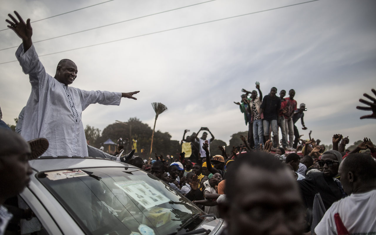 Adama Barrow, the flag-bearer of the coalition of the seven opposition political parties in Gambia, greets supporters from the roof of his car at a gathering in the buffer Zone district of Talinding on November 29, 2016 on the last day of the presidential campaign in Gambia. Gambian opposition leader Adama Barrow said on November 29 he believed his coalition would sweep the presidential election in two days time following unprecedented rallies nationwide, and urged President Yahya Jammeh to go peacefully if he loses power. The businessman emerged from obscurity to become the flagbearer of all The Gambia's opposition parties bar one after mass arrests of supporters from the largest anti-government grouping in April / AFP PHOTO / MARCO LONGARI