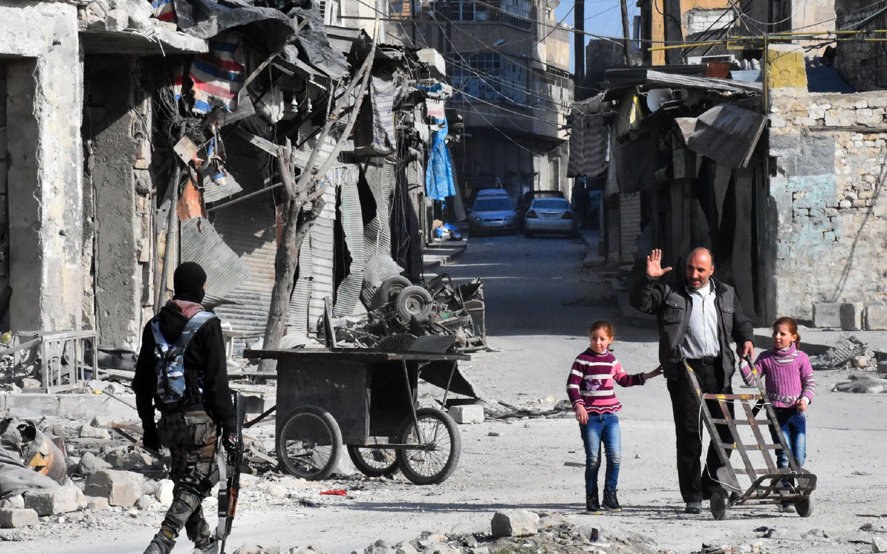 "A man waves to a member of the Syrian pro-government forces patrolling a street in the newly retaken Bab al-Hadid neighbourhood in Aleppo's Old City on December 8, 2016. President Bashar al-Assad said victory for his forces in Aleppo would be a ""huge step"" in ending Syria's war, as government troops battled to retake more rebel ground. Regime forces have retaken about 80 percent of former rebel territory in Aleppo since launching an all-out offensive three weeks ago to recapture Syria's second city. / AFP PHOTO / GEORGE OURFALIAN"