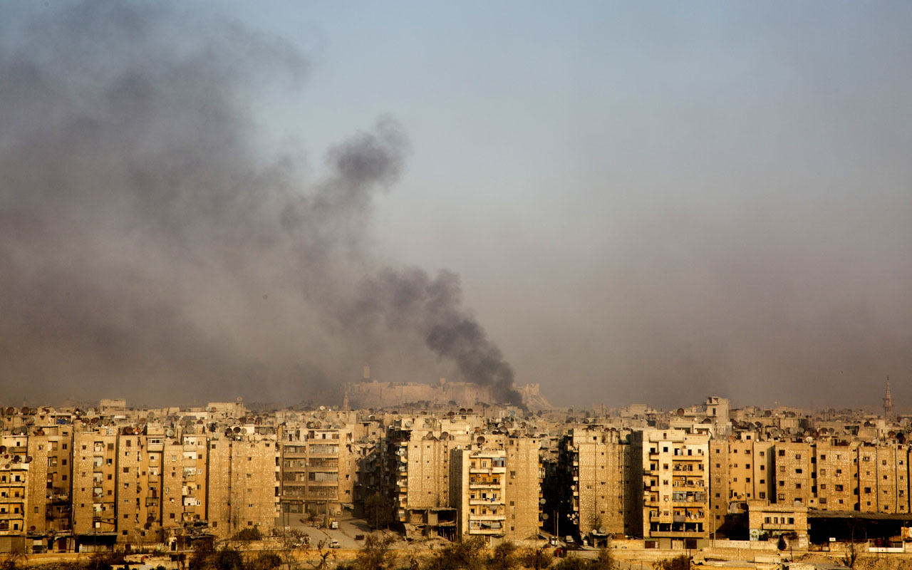 "Smoke billows from the former rebel-held district of Bustan al-Qasr in Aleppo, on December 12, 2016, during an operation by Syrian government forces to retake the embattled city. The crucial battle for Aleppo entered its ""final phase"" after Syrian rebels retreated into a small pocket of their former bastion in the face of new army advances. The retreat leaves opposition fighters confined to just a handful of neighbourhoods in southeast Aleppo, the largest of them Sukkari and Mashhad. / AFP PHOTO / KARAM AL-MASRI"