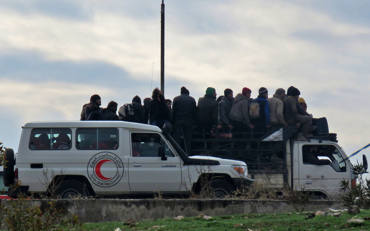 Staff from the Syrian Red Crescent are seen as civilians and fighters are evacuated from a rebel-held area of Aleppo towards rebel-held territory in the west of Aleppo's province on December 16, 2016. Russia announced it was negotiating with the Syrian opposition and seeking a nationwide ceasefire, as the evacuation of civilians and fighters from the last rebel-held parts of Aleppo entered a second day. The Syrian Observatory for Human Rights, a Britain-based monitor of the war, estimated some 8,500 people had left so far, including around 3,000 rebel fighters. Syrian state media reported a figure of around 8,000. / AFP PHOTO / STRINGER