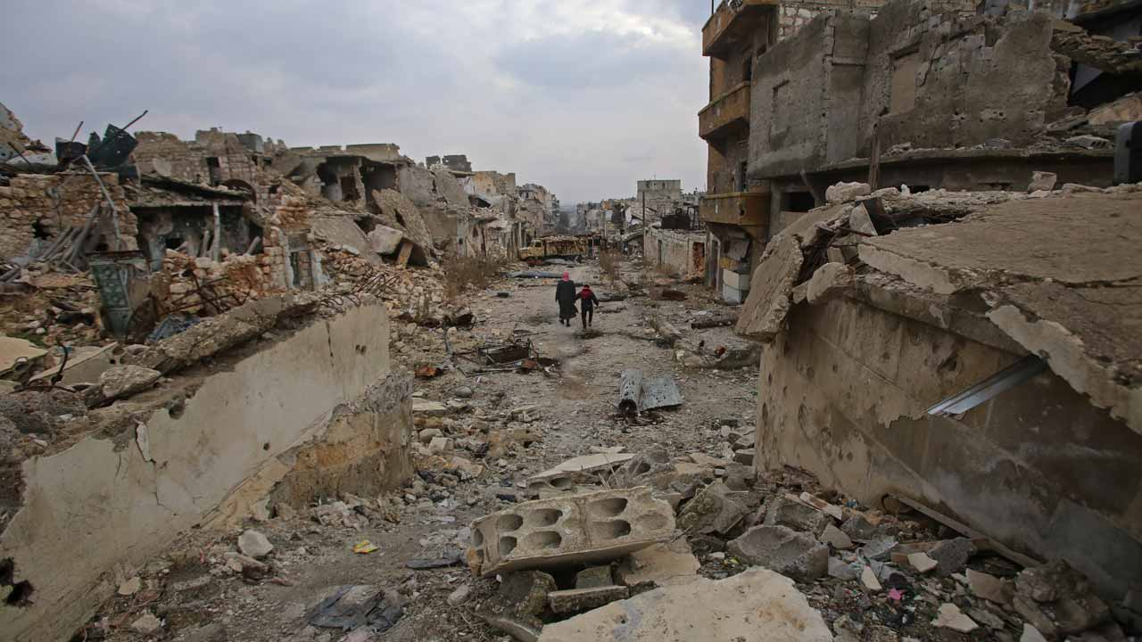 Syrians walk down a destroyed street in Aleppo's al-Akroub neighbourhood on December 17, 2016.  Youssef KARWASHAN / AFP