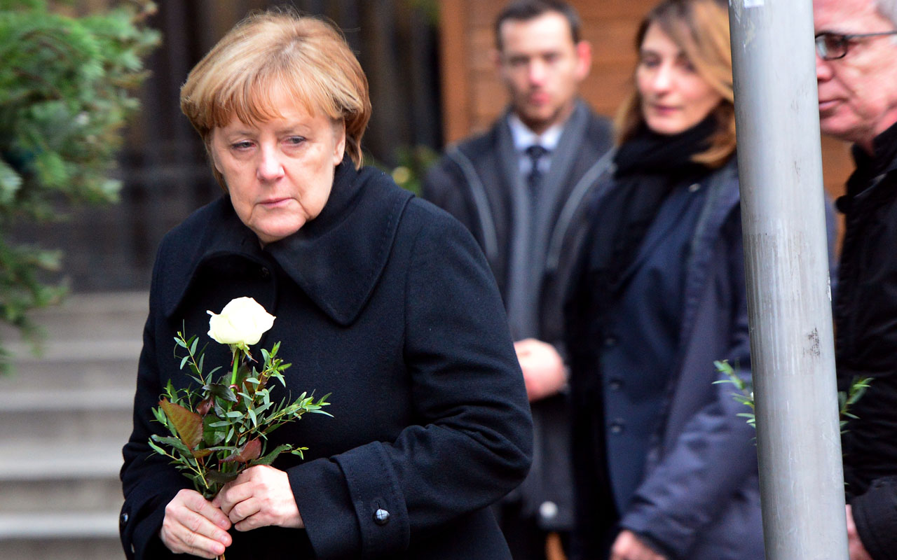 German Chancellor Angela Merkel (L) is about to lay flowers with German Interior Minister Thomas de Maiziere (R) on December 20, 2016 at the site where a truck crashed into a Christmas market near the Kaiser-Wilhelm-Gedaechtniskirche (Kaiser Wilhelm Memorial Church) in Berlin. Twelve people were killed and almost 50 wounded, 18 seriously, when the lorry tore through the crowd on December 19, 2016, smashing wooden stalls and crushing victims, in scenes reminiscent of July's deadly attack in the French Riviera city of Nice. / AFP PHOTO / dpa / Maurizio Gambarini / Germany OUT