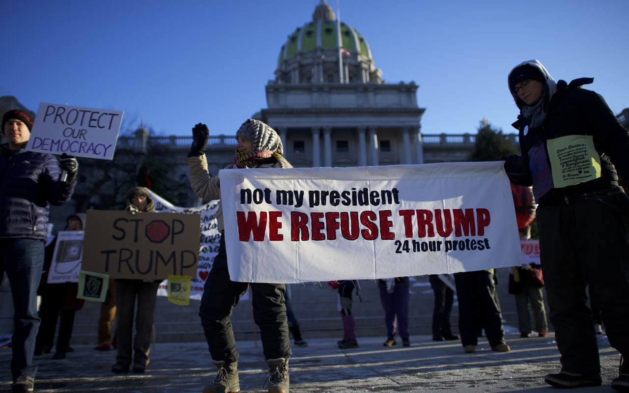 HARRISBURG, PA - DECEMBER 19: Donald Trump protestors demonstrate outside the Pennsylvania Capitol Building before electors arrive to cast their votes from the election at December 19, 2016 in Harrisburg, Pennsylvania. Electors from all 50 states cast votes today in their respective state capitols. Donald J. Trump won Pennsylvania by less than 1%, the first Republican to carry the state since George H.W. Bush 1992. Mark Makela/Getty Images/AFP