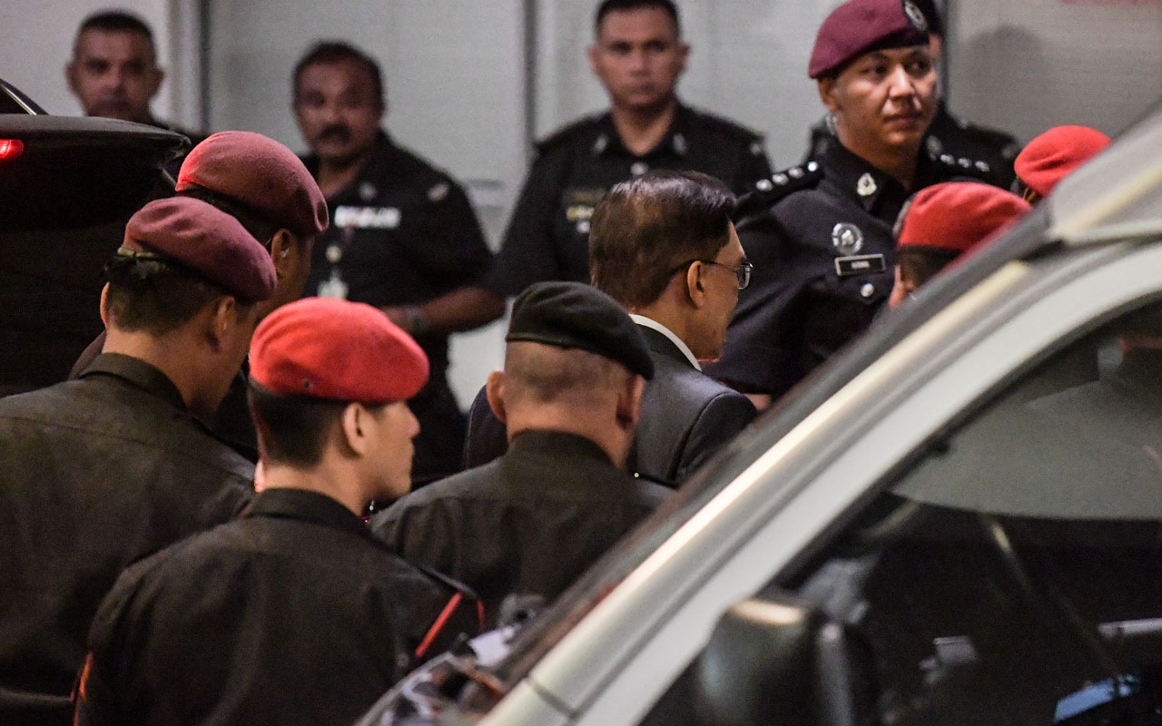 Jailed Malaysian politician Anwar Ibrahim (2nd R) is escorted by prison security during his arrival at the federal court in Putrajaya on December 14, 2016. Former Malaysian opposition leader Anwar Ibrahim will remain in jail after the country's highest court on December 14 rejected his bid for a review of his controversial 2014 sodomy conviction. / AFP PHOTO / MOHD RASFAN