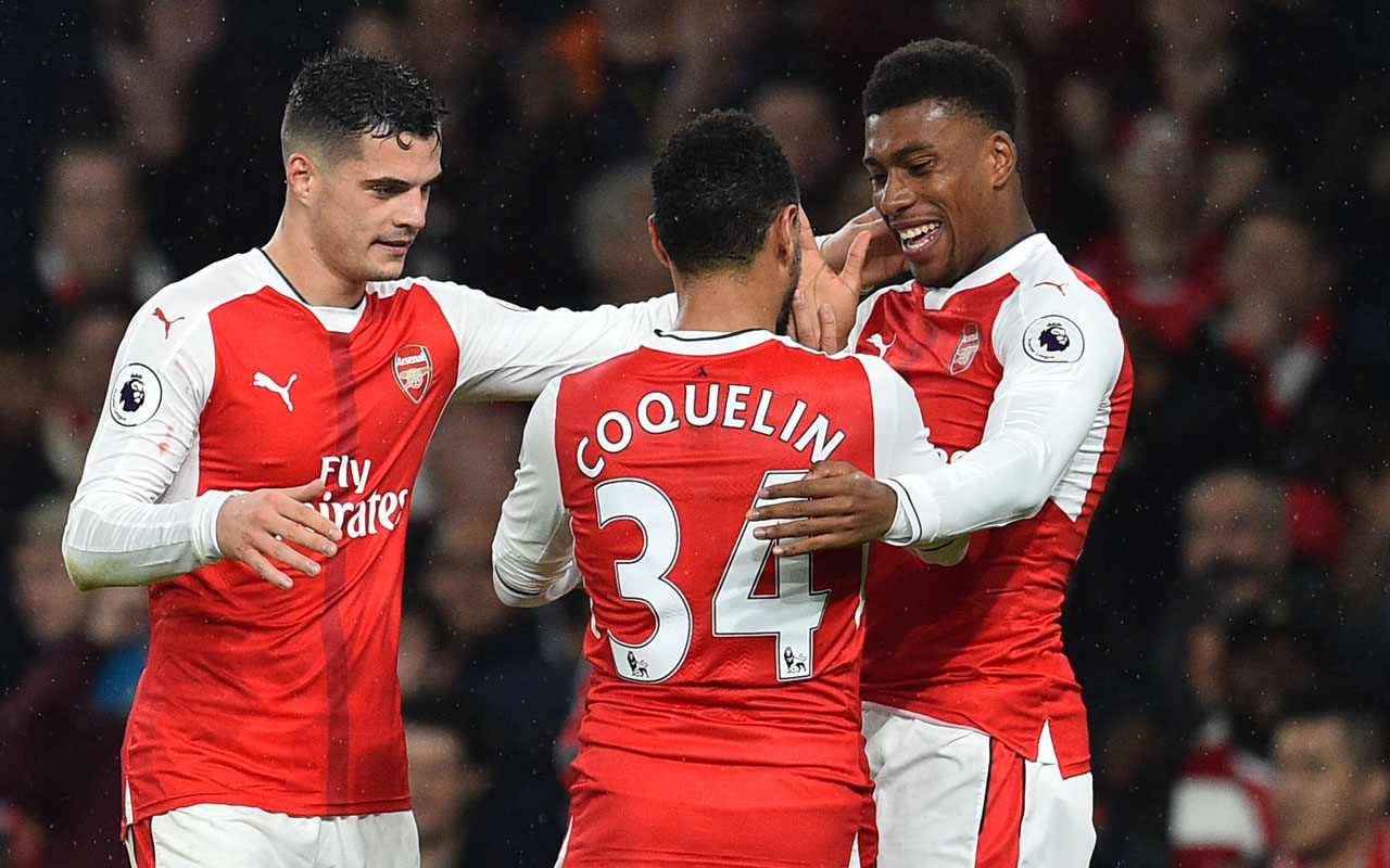 Arsenal's Nigerian striker Alex Iwobi (R) celebrates with teammates after scoring their third goal during the English Premier League football match between Arsenal and Stoke City at the Emirates Stadium in London on December 10, 2016. / AFP PHOTO / Glyn KIRK /
