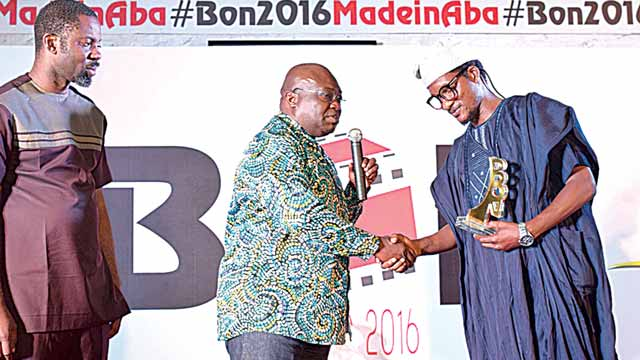 Founder of BON, Seun Oloketuyi looks on, as Gov. Ikpeazue presents award to Fidelis Duker.