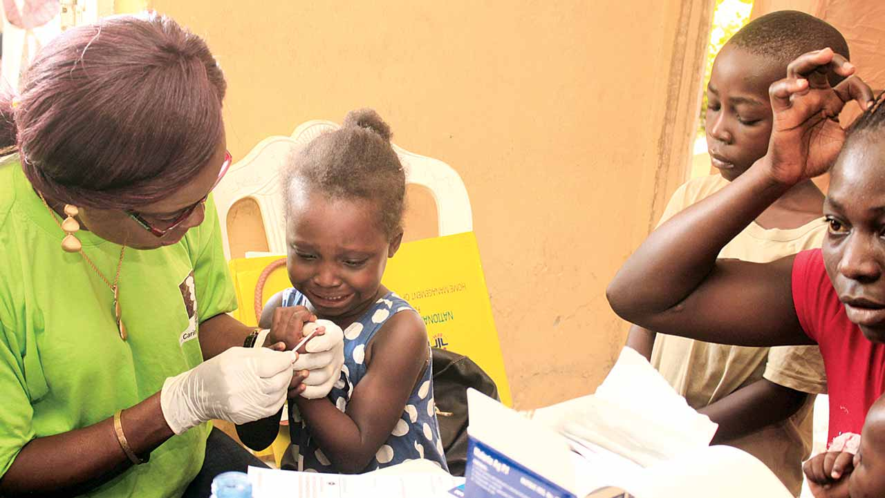 A medical personnel taking blood sample from a child during a recent health fair organised by Pfizer Nigeria in partnership with the Society of St. Vincent de Paul, at Victoria Garden City