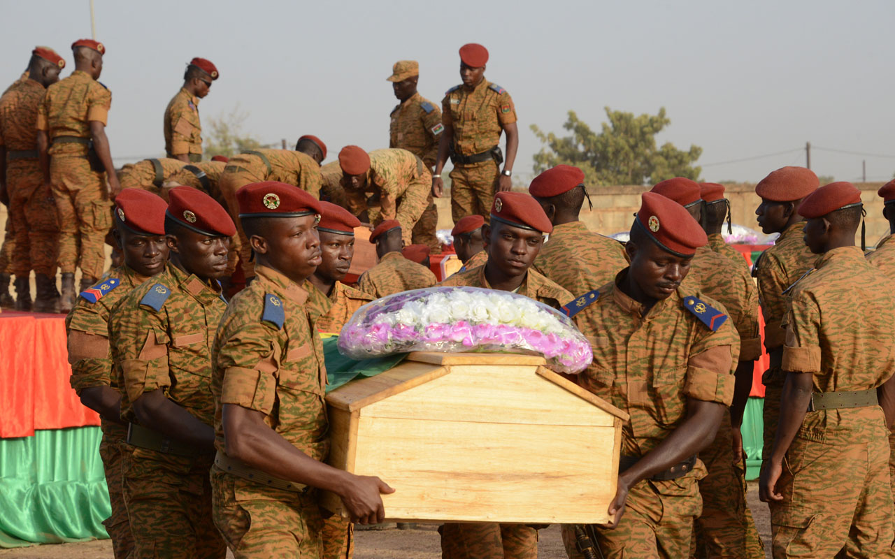 Soldiers of the Burkina Faso's Armed Forces carry the coffin of servicemen killed during an attack in Nassoumbou few days ago, at the cemetery in Ouagadougou on December 20, 2016. Mali's president said on December 20 he could let Burkina Faso forces pursue jihadist fighters when they flee across the border into his country, days after militants massacred 12 Burkinabe soldiers. Around 40 fighters attacked a base some 30 kilometres (18 miles) from the Burkina-Mali border on December 16 in what local authorities called the biggest ever jihadist attack on the army. / AFP PHOTO / Ahmed OUOBA