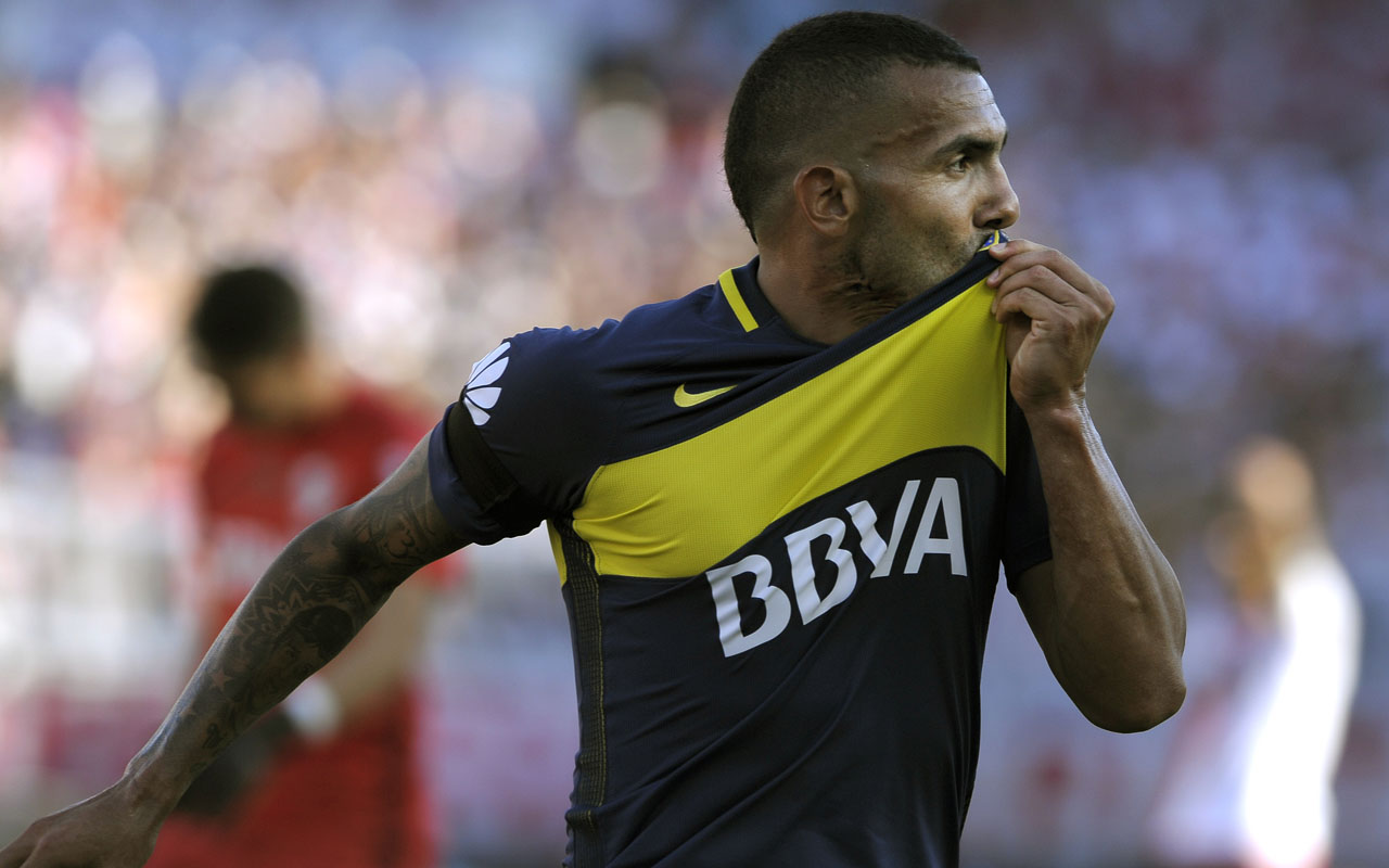(FILES) This file photo taken on December 11, 2016 shows Boca Juniors' forward Carlos Tevez celebrating after scoring the team's second goal against River Plate during their Argentina First Division football match at El Monumental stadium in Buenos Aires. Argentina's former Manchester United and Manchester City striker Carlos Tevez has signed for Shanghai Shenhua in the latest big-money Chinese deal, the club said on December 29, 2016, reportedly making him the world's best-salaried footballer. / AFP PHOTO / ALEJANDRO PAGNI