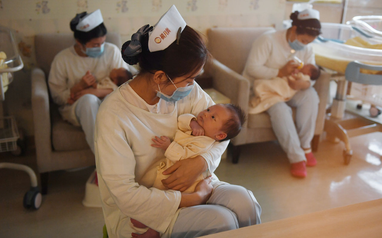 "This photo taken on December 13, 2016 shows nurses holding babies at the Xiyuege Centre, or ""Lucky Month Home"", in Beijing. Since the late 70s, strict measures in the world's most populous country restricted most couples to only a single offspring with a system of fines for violators and even forced abortions. But concerns over an ageing population, gender imbalances and a shrinking workforce pushed authorities to end the restriction, allowing all couples a second child from January 1. / AFP PHOTO / Greg Baker / TO GO WITH China population politics children social, FOCUS by Becky DAVIS"