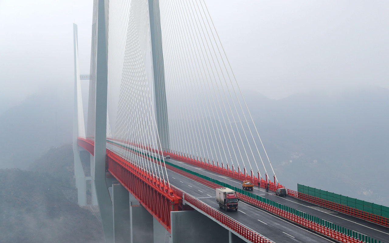 This picture taken on December 29, 2016 shows vehicles making their way through the Beipanjiang Bridge, near Bijie in southwest China's Guizhou province.   The world's highest bridge has opened to traffic in China, connecting two southwestern provinces and reducing travel time by three quarters, local authorities said on December 30. / AFP PHOTO / STR / China OUT