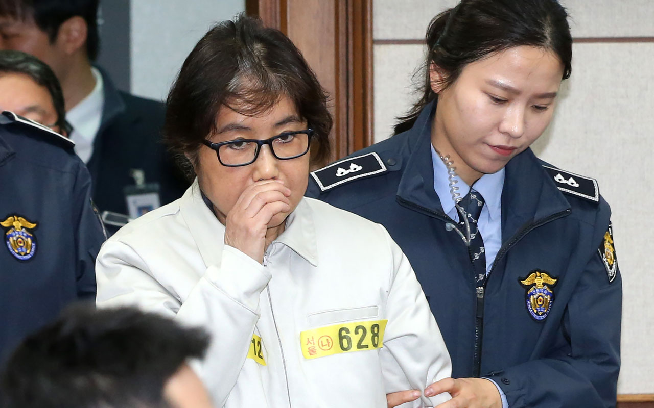 "Choi Soon-Sil (C), who has been dubbed Korea's ""female Rasputin"" for the influence she wielded over the now-impeached president Park Geun-Hye, arrives at a courtroom for her trial at the Seoul Central District Court in Seoul on December 19, 2016. The woman at the centre of a corruption scandal that triggered the biggest political crisis for a generation in South Korea appeared in court on December 19 for a preliminary hearing in her trial on fraud charges. / AFP PHOTO / KOREA POOL / KOREA POOL / South Korea OUT"