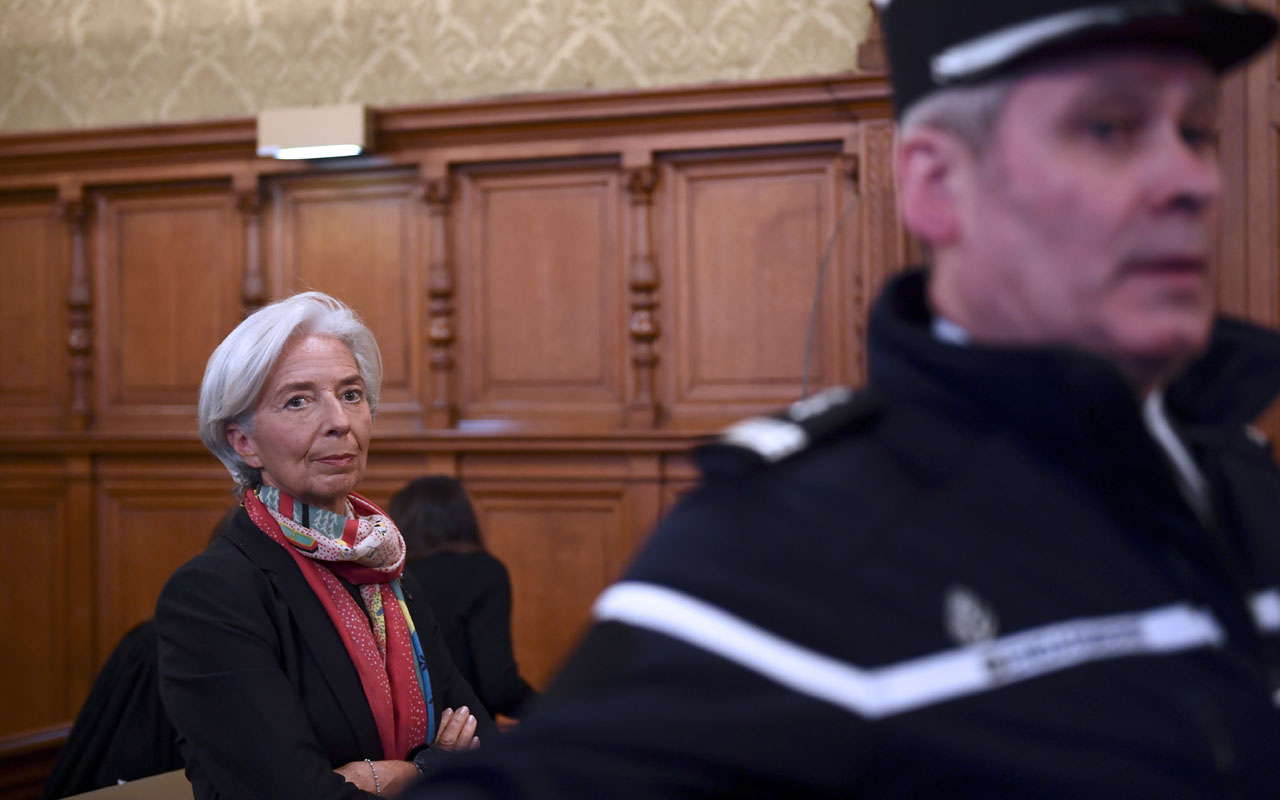 IMF chief Christine Lagarde is pictured next to a Gendarme in the courtroom at the Paris courthouse on December 12, 2016 prior to the start of her trial before the Court of Justice of the Republic, a special tribunal used to try ministers. IMF chief Christine Lagarde goes on trial in France on December 12 over a massive state payout to a flamboyant tycoon when she was finance minister in a case that risks tarnishing her stellar career. / AFP PHOTO / Martin BUREAU