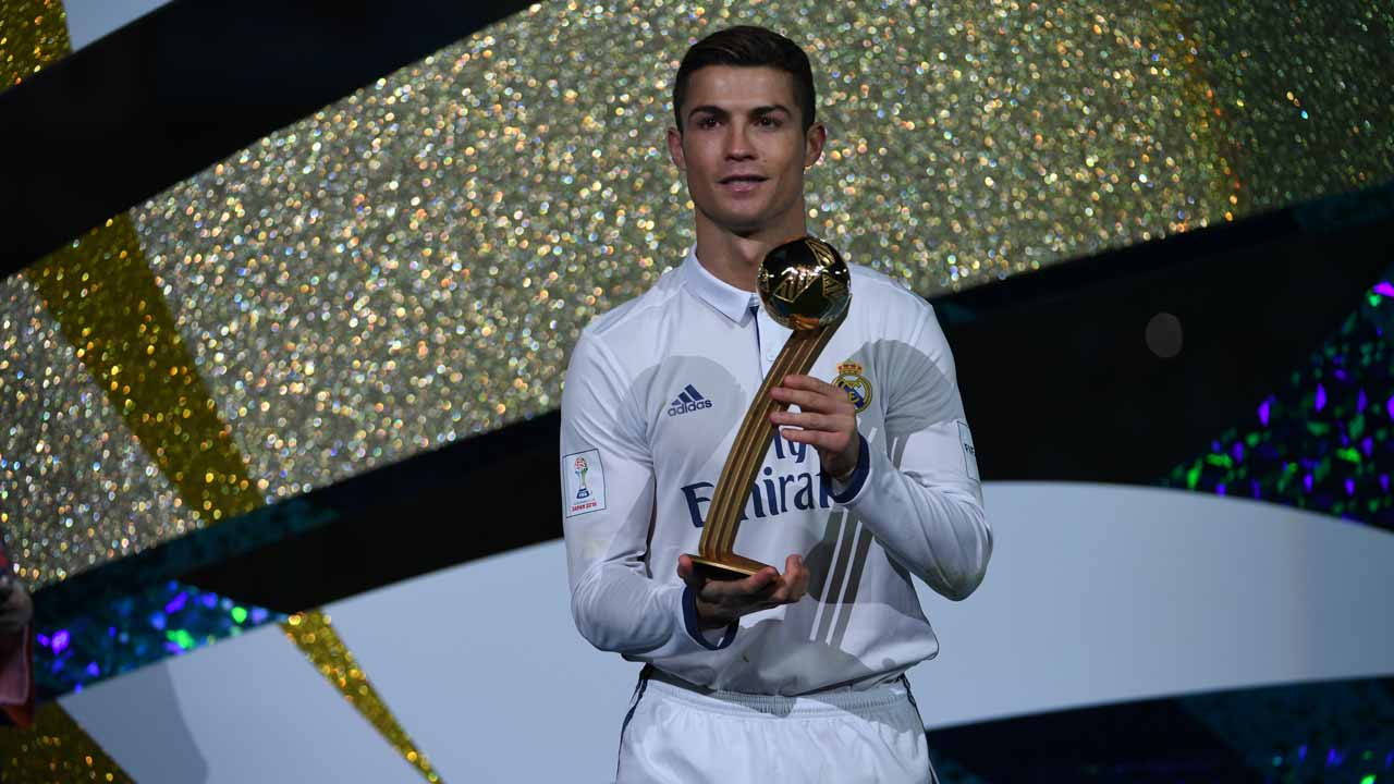 Real Madrid's forward Cristiano Ronaldo poses as he holds the Golden Ball trophy after winning the Club World Cup football final match between Kashima Antlers of Japan and Real Madrid of Spain at Yokohama International stadium in Yokohama on December 18, 2016.  Toshifumi KITAMURA / AFP