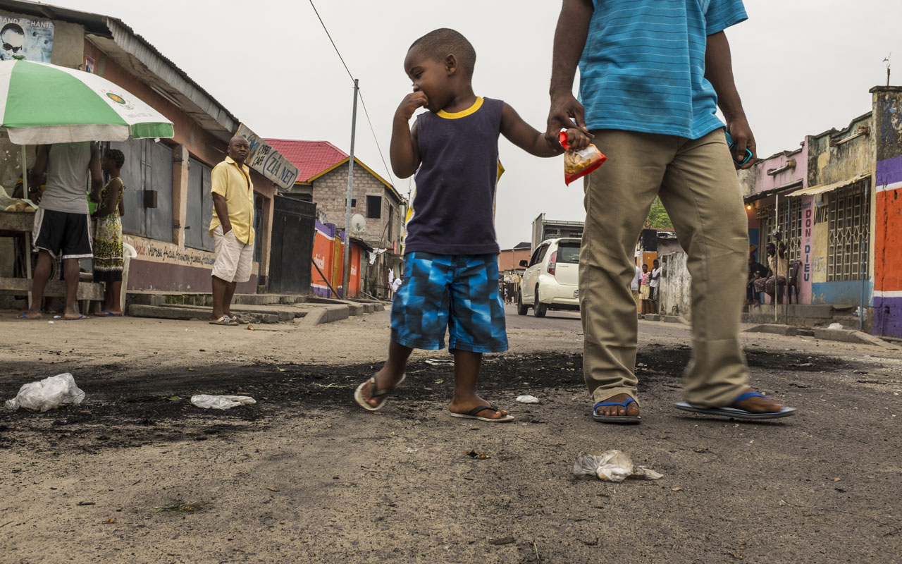 A child stares at the marks of burnt tyres following a protest in the Lingwala neighborhood in Kinshasa on December 20, 2016. Gunfire was heard in DR Congo's two largest cities as the opposition leader called on citizens to reject President Joseph Kabila whose mandate expired on December 20 with no sign he was ready to leave. With fears of fresh violence high in the vast and unstable nation, shots rang out in the capital Kinshasa and the country's second city of Lubumbashi. / AFP PHOTO / Eduardo Soteras