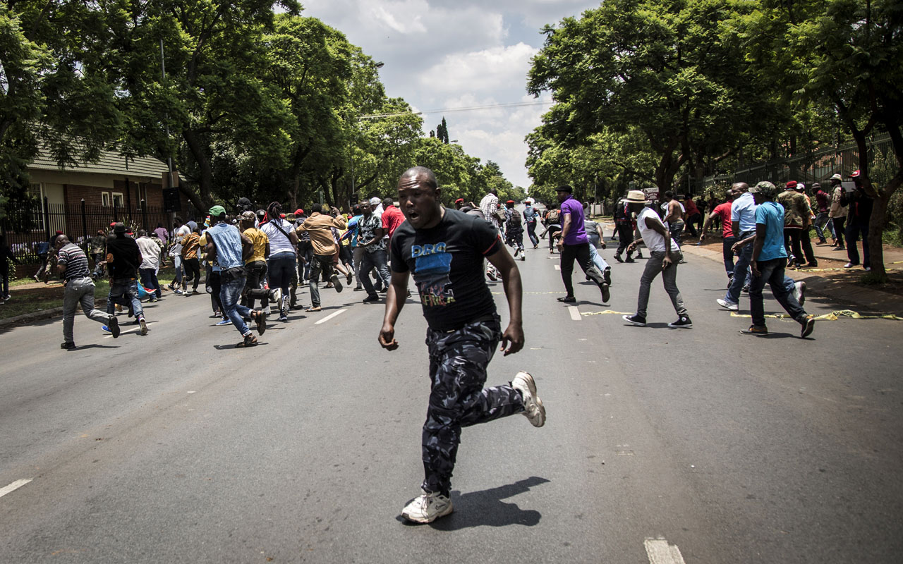 Congolese protesters scatter as police open fire with rubber bullets whilst they protest outside the Democratic Republic of the Congo's Embassy in defiance of their President, Joseph Kabila on December 20, 2016 in Pretoria. The United Nations voiced alarm over a wave of arrests in the Democratic Republic of Congo, where tensions were running high after President Joseph Kabila's term in office expired. Tuesday marked the end of the second and constitutionally-mandated final term for the 45-year-old, who inherited the presidency after the 2001 assassination of his father. But he is now refusing to leave the job that he began without much fanfare. / AFP PHOTO / John Wessels