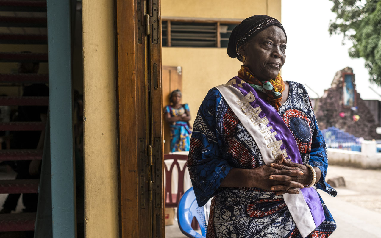 A woman stands at the door of the Saint Raphael Parish in Kinshasa on December 18, 2016.  Security forces patrolled the tense streets of Kinshasa on December 18 after the suspension of last-ditch talks to find a peaceful way out of the nation's political crisis sparked by the end of President Joseph Kabila's mandate. / AFP PHOTO / Eduardo Soteras