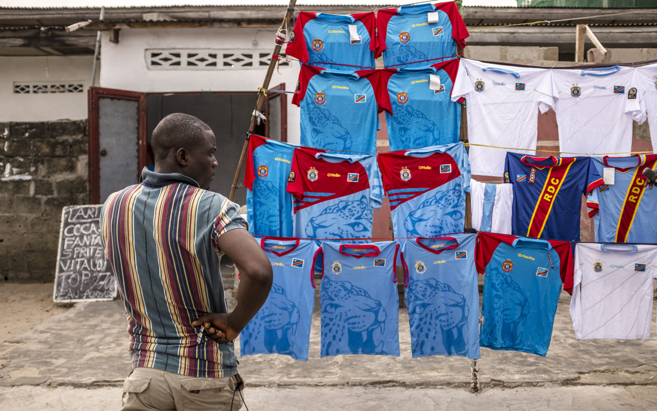 A man stands next to a stall selling Congolese national football team teeshirts in Kinshasa, on December 21, 2016. At least 11 people died as gunfire erupted during protests on December 20, 2016 in Democratic Republic of Congo against longtime President Joseph Kabila, who is refusing to leave office as his mandate ends. Tension has been mounting for months in DR Congo ahead of the December 20 deadline for Kabila's second and final term in office to end. / AFP PHOTO / Eduardo Soteras