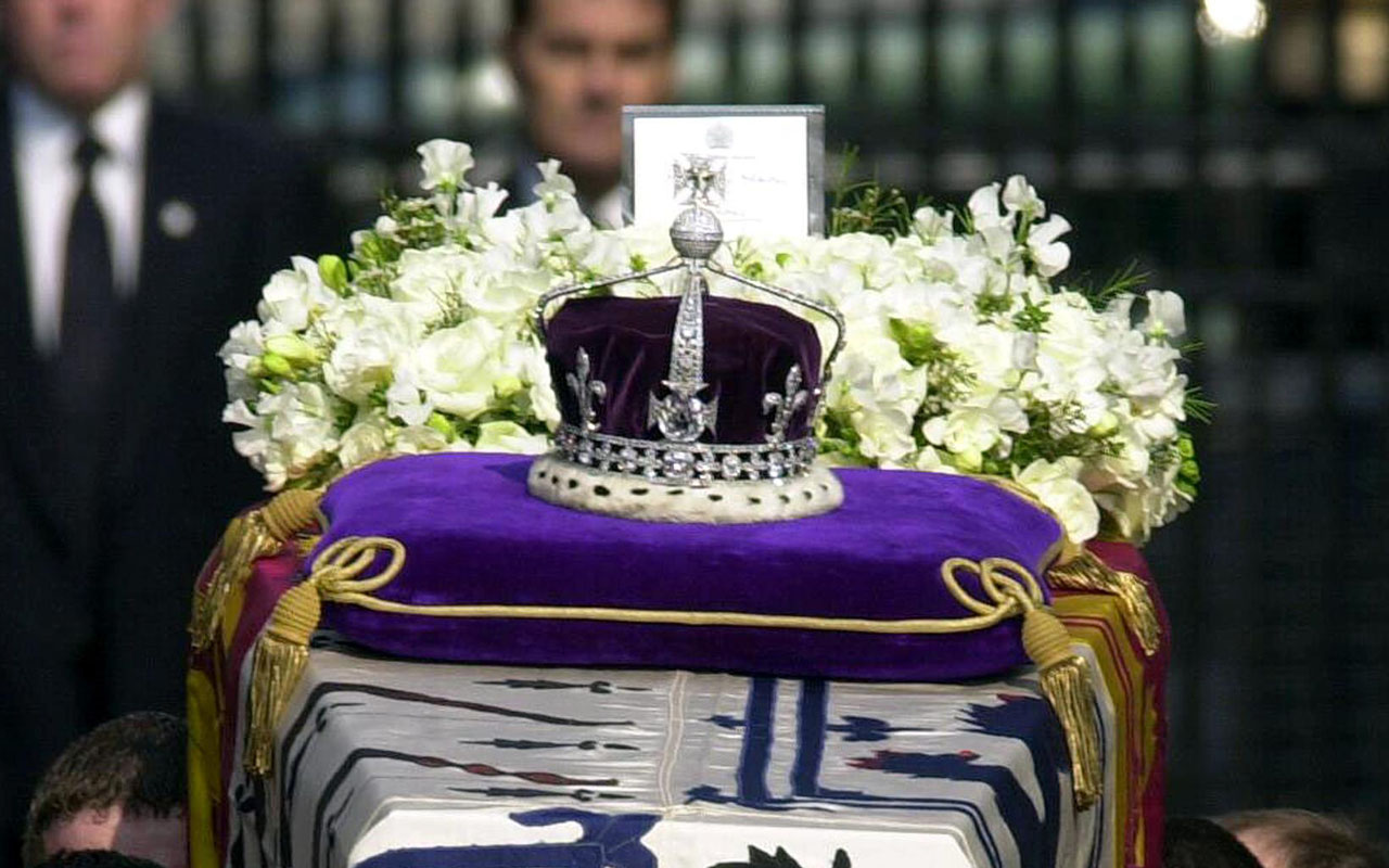 "This file photo taken on April 5, 2002 shows the Crown Jewels atop the standard-draped coffin of Queen Elizabeth the Queen Mother as it is taken out of Queen's Chapel, St. James' Palace, in central London, carried by soldiers of the Royal Irish Guards, on its way to Westminster Hall. Many precious stones have a blood-soaked history, but a new book reveals the world's most famous diamond the Koh-i-Noor surpasses them all, with a litany of horrors that rivals ""Game of Thrones"". / AFP PHOTO / POOL / TOBY MELVILLE /"