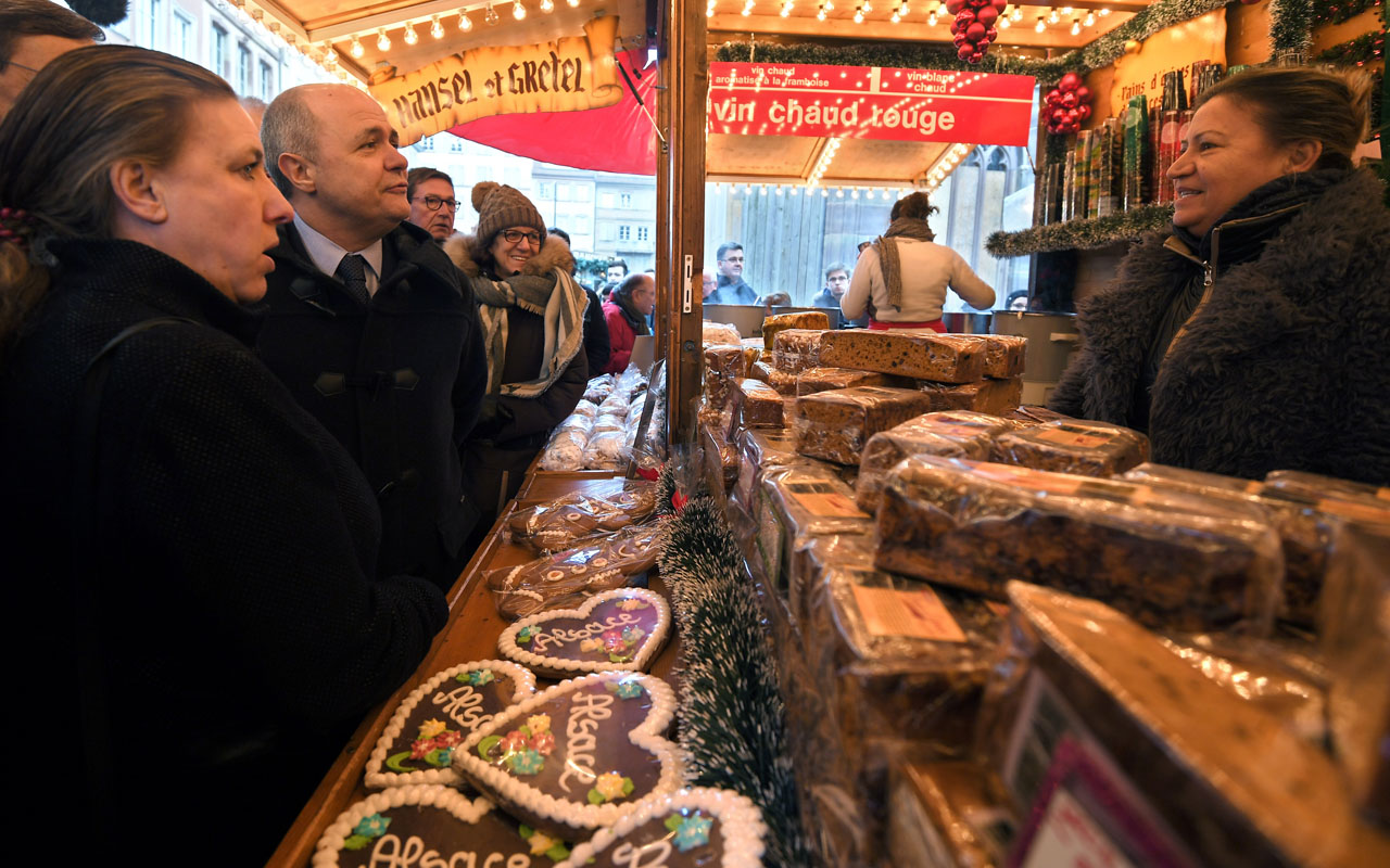 French Interior Minister Bruno Le Roux (L) speaks with a gingerbread stall keeper as he reviews security measures at a Christmas market in Strasbourg, eastern France, on December 20, 2016. The Christmas market in Strasbourg, one of the largest and most famous in Europe, opened on November 25, 2016 under tightened security, with two million people expected to visit over four weeks. / AFP PHOTO / PATRICK HERTZOG