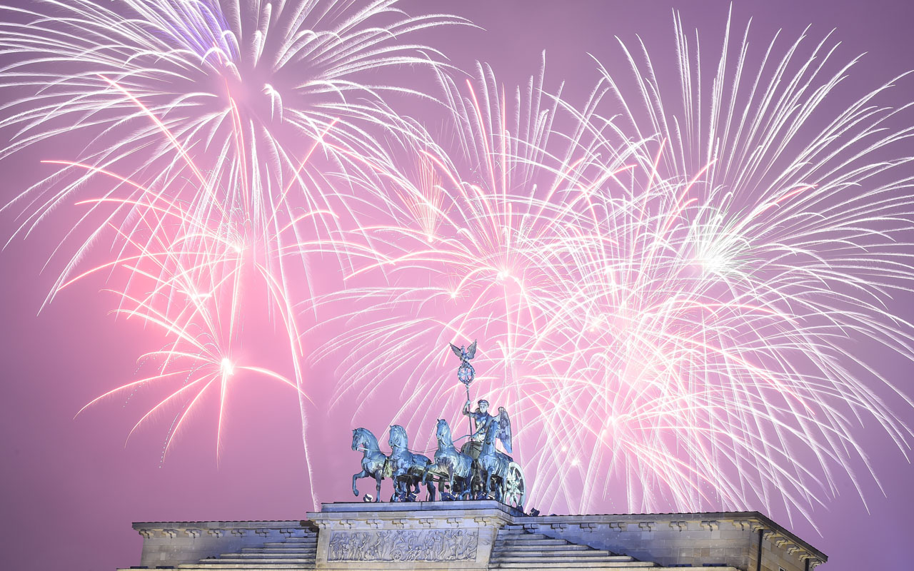 (FILES) This file photo taken on January 1, 2016 shows fireworks exploding behind the quadriga statue of Berlin's Brandenburg Gate to usher in the new year. German authorities are beefing up security for New Year's eve celebrations in Berlin on December 31, 2016 after the truck attack from December 19, 2016, deploying police with machine guns and securing the festive zone around the Brandenburg Gate with concrete slabs. / AFP PHOTO / TOBIAS SCHWARZ