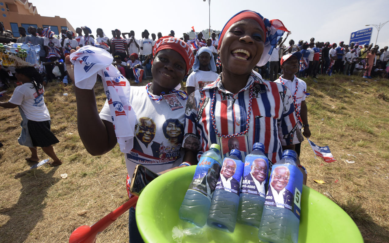Supporters sell water bottles with the portrait of presidential candidate of leading opposition New Patriotic Party (NPP) Nana Akufo-Addo, during a campaign rally in Accra, on December 4, 2016, ahead of the December 7 presidential election. Ghana's New Patriotic Party (NPP) candidate Nana Akufo-Addo is hoping it'll be third time lucky when the country votes for a new president on December 7. Akufo-Addo, an erudite rights lawyer and former government minister with round tortoiseshell glasses, narrowly lost the 2008 and 2012 elections to the ruling National Democratic Congress (NDC). / AFP PHOTO / PIUS UTOMI EKPEI