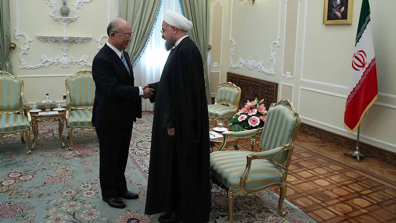A handout picture provided by the office of Iranian President Hassan Rouhani on December 18, 2016 shows him (R) greeting Yukiya Amano (L), Director General of the International Atomic Energy Agency (IAEA), ahead of their meeting in the capital Tehran.  HO / IRANIAN PRESIDENCY / AFP