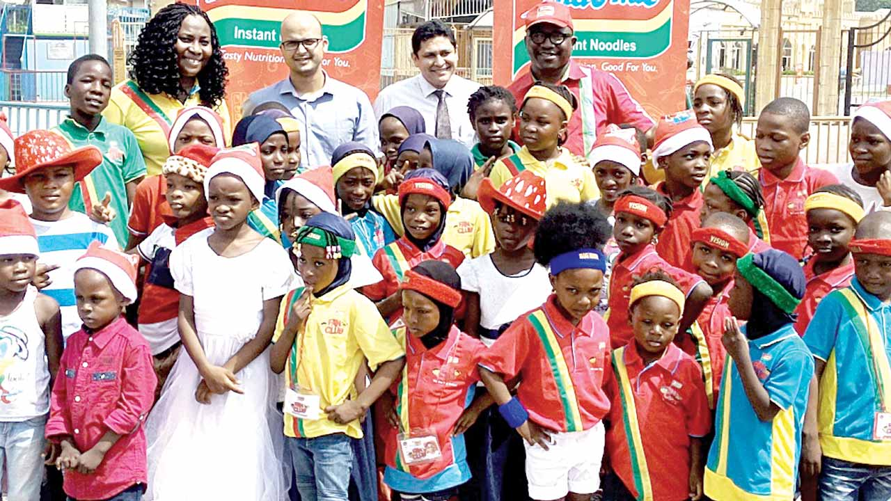 Joshua (left); Brand Manager, Indomie, Mr Amber Yadav; General Manager, Dufil Prima Foods Plc, Mr Girish Sharma, Ashiwaju with a cross section of kids at the IFC Xmas/End of the Year Party in Lagos....yesterday