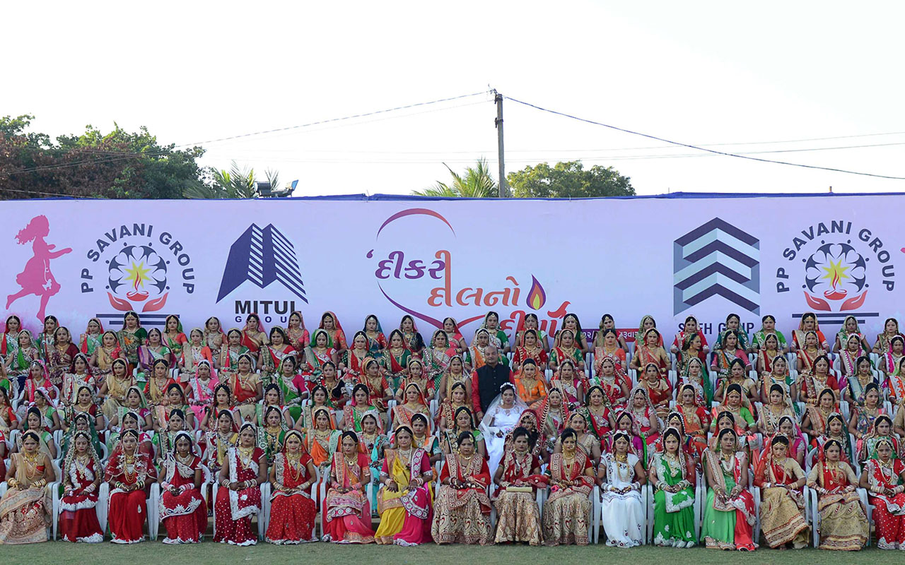 Participants pose for a photo at the mass wedding of 236 fatherless girls organised by the charitable PP Savani Group in Surat, some 270 km from Ahmedabad, on December 25, 2016. Out of 236 fatherless girls married in the mass wedding event, five were from the Muslim community, and one Christian, with the majority being Hindus.  / AFP PHOTO / SAM PANTHAKY