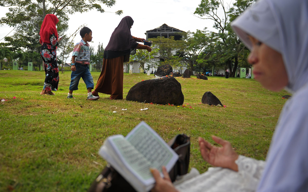 "Family members gather to offer prayers for loved ones at a mass grave in Aceh on December 26, 2016, to mark the tsunami which devastated Aceh province 12 years ago in one of the worst natural disasters in human history. Some 170,000 lives were lost in the country when a 9.1-magnitude ""megathrust"" quake struck Aceh, a predominantly Muslim province in the northern tip of Sumatra island, bringing about massive waves that also hit coastal areas as far away as Somalia. / AFP PHOTO / CHAIDEER MAHYUDDIN"