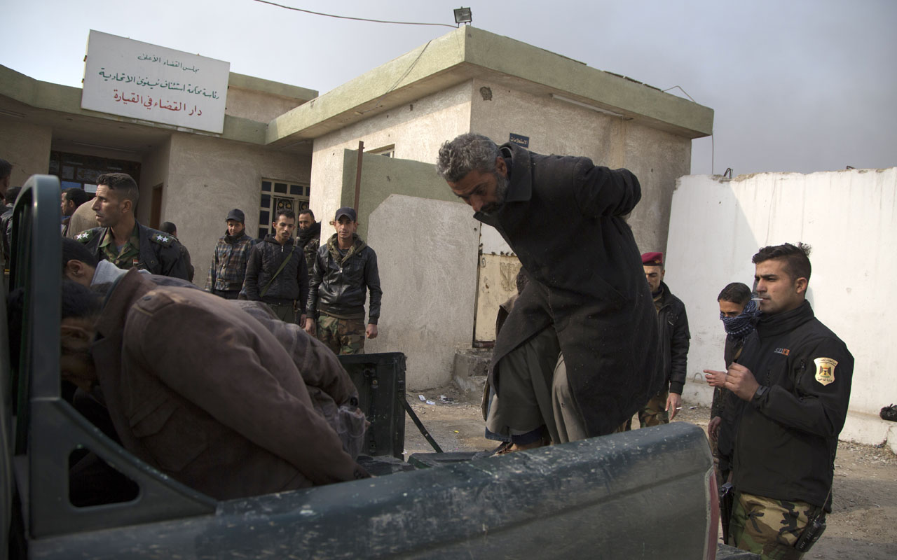 Members of the Iraqi army assist suspected Islamic State group (IS) jihadists to get into a pick up as they leave the House of Justice before going to jail on December 6, 2016 in the town of Qayyarah, south of Mosul. Since starting an offensive on October 17 to oust the Islamic State group from its last Iraqi stronghold of Mosul, pro-government forces say they have recaptured 40 percent of the eastern half of the city and are edging towards the Tigris river that divides it. / AFP PHOTO / Gailan Haji
