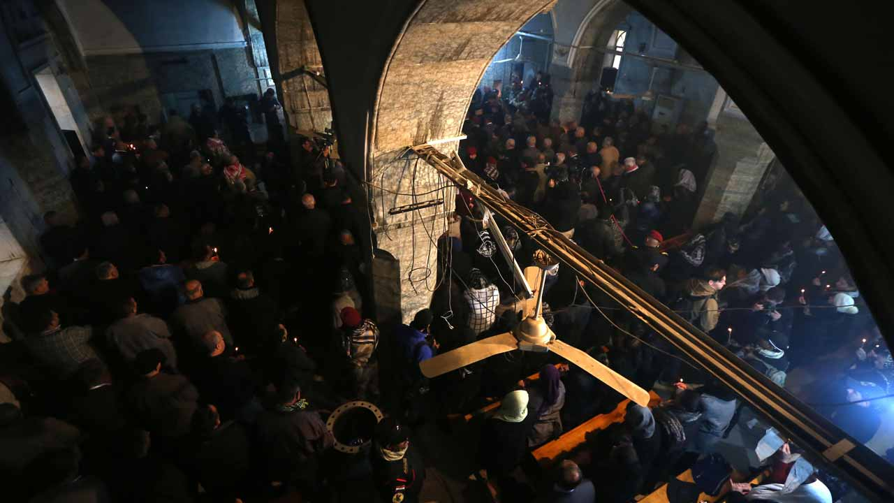 raqi Christians attend a Christmas Eve service at the Mar Shimoni church in the town of Bartalla near Mosul, on December 24, 2016, for the first time since its recapture from Islamic State (IS) jihadists. IS seized Bartalla and swathes of other territory north and west of Baghdad in the summer of 2014, leaving Christians with the grim choices of conversion, paying a tax, fleeing or death. The town was recaptured as part of the massive military operation to retake Mosul, the last IS-held Iraqi city, which was launched on October 17. SAFIN HAMED / AFP