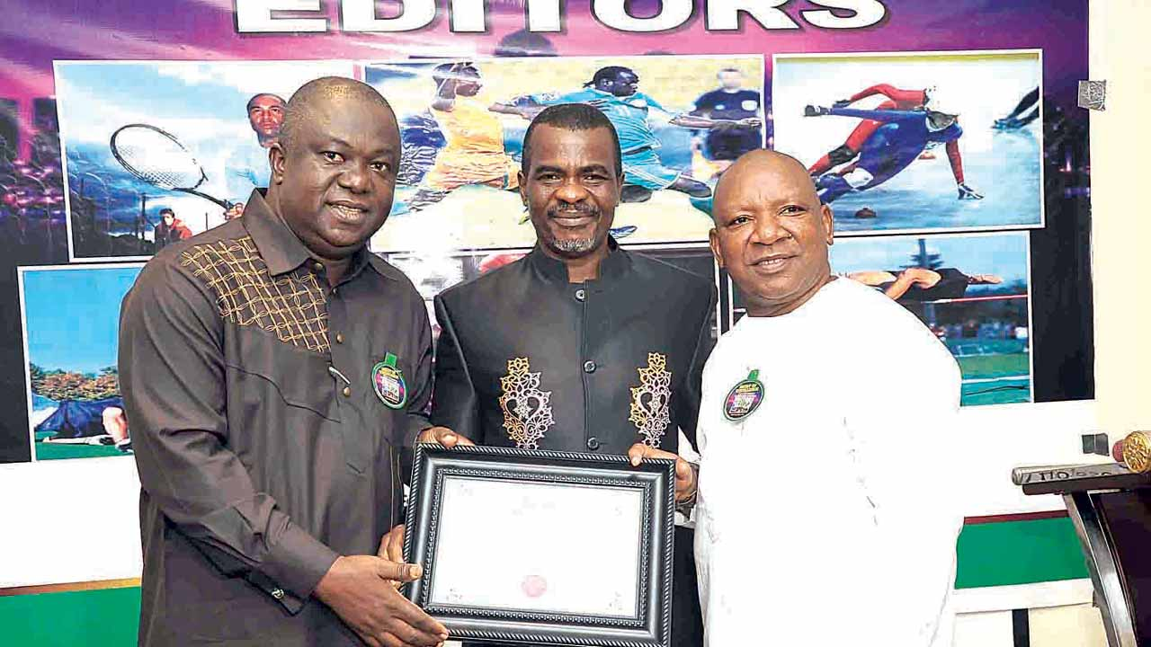 Proprietor of Sports Radio Brilafm, Dr. Larry Izamoje (left), receiving his award from AIPS Africa President, Mitchel Obi and Guild of Sports Editors' President, Tony Ubani, at the Night of Excellence held in Lagos…on Tuesday.