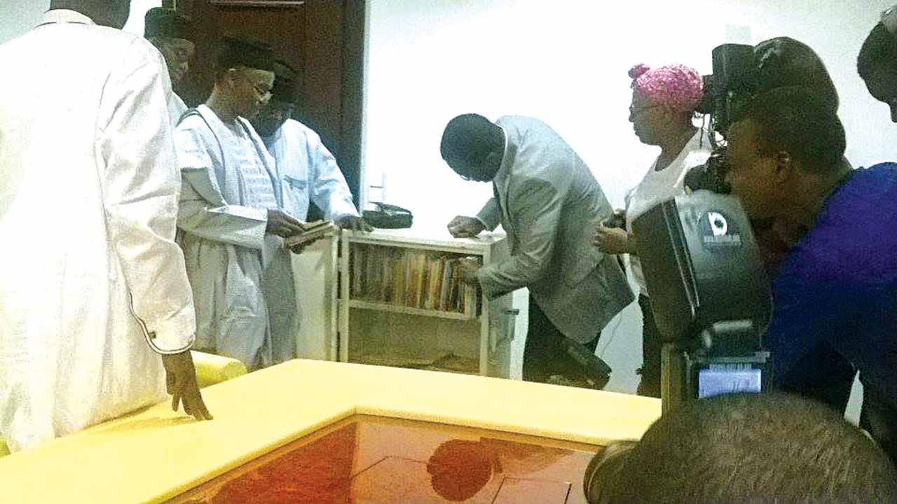 Governor of Kaduna State, Malam Nasir El Rufai admiring the books (left); his Commissioner for Education, Prof. Jonathan Nok watches on as Mr. Abaji Nyam of Marine Platform (with Lola Shoneyin behind him) showing off the mobile library with 100 hundred books donated to primary schools in the state