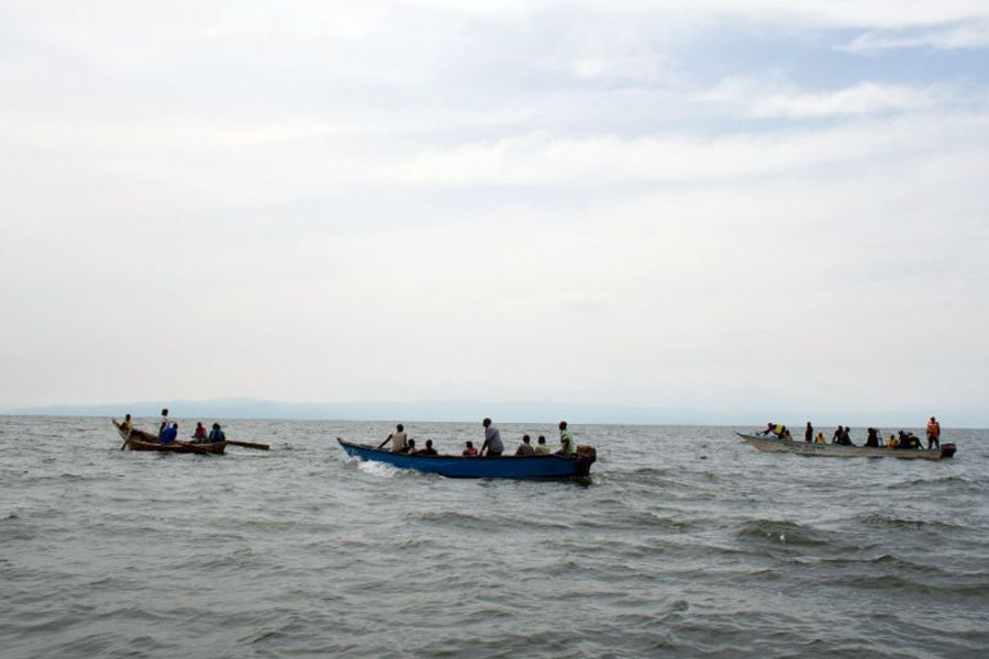 Uganda Police divers and local fishermen search for victims of a boat disaster on Lake Albert near Kitebere on March 23, 2013 (AFP Photo/Michele Sibiloni)