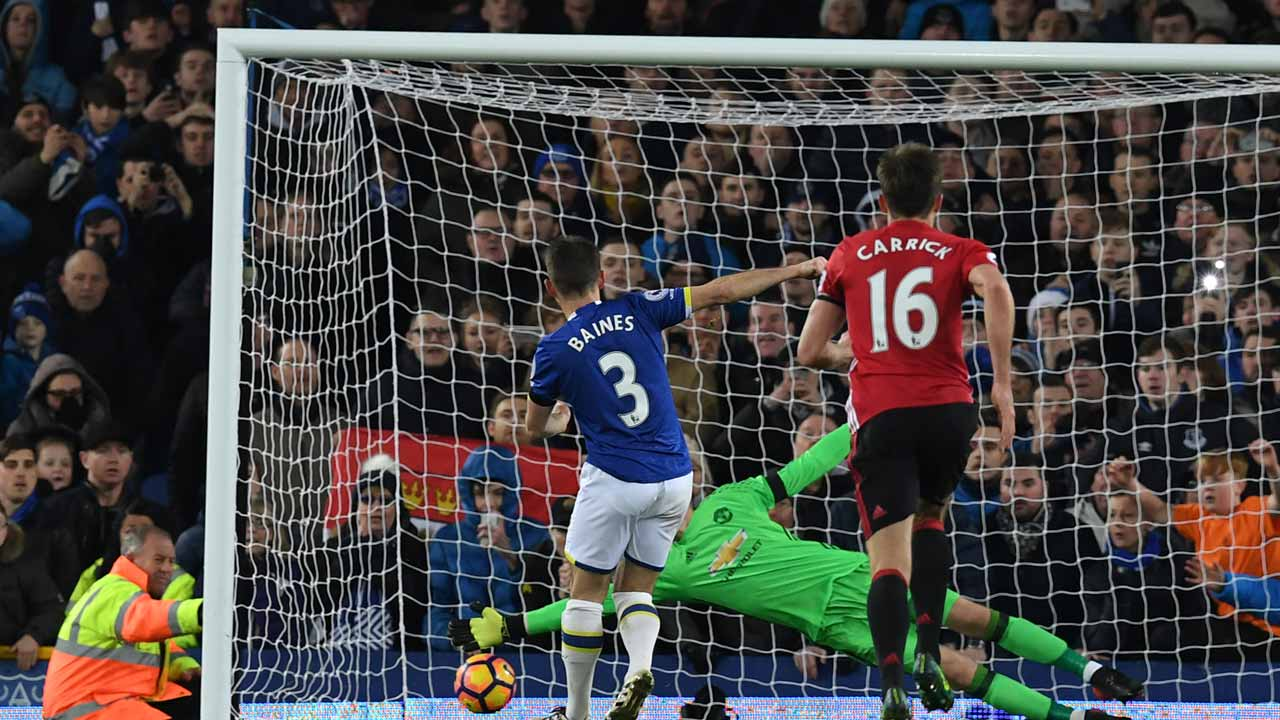 Everton's English defender Leighton Baines (L) scores his penalty past the diving Manchester United's Spanish goalkeeper David de Gea during the English Premier League football match between Everton and Manchester United at Goodison Park in Liverpool, north west England on December 4, 2016. The game ended 1-1. Paul ELLIS / AFP