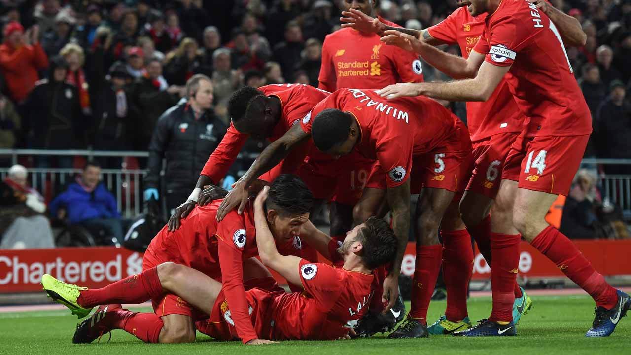 Liverpool's Brazilian midfielder Roberto Firmino (L) celebrates with team-mates including Liverpool's English midfielder Jordan Henderson (R) and Liverpool's English midfielder Adam Lallana (floor) after scoring their second goal during the English Premier League football match between Liverpool and Stoke City at Anfield in Liverpool, north west England on December 27, 2016. Paul ELLIS / AFP