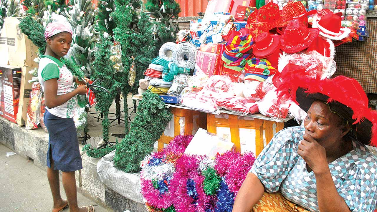 A woman selling Christmas wares along Martins Street, Idumota, Lagos State, awaits buyers that are nowhere to be found, yesterday. PHOTO: AYODELE ADENIRAN