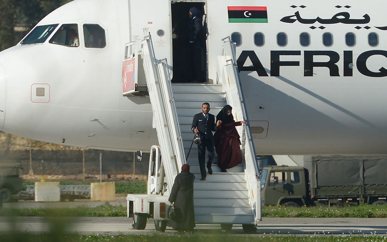 "A picture taken on December 23, 2016 in Valletta, Malta, shows a crew member helping hostages to disembark from the Afriqiyah Airways A320 after it was hijacked from Libya. A man who said he was armed with a grenade hijacked a Libyan plane which landed on Malta Friday with 118 people on board, Malta's prime minister and government sources on the Mediterranean island said. After more than an hour on the tarmac, the plane's door opened and a first group of women and children were seen descending a mobile staircase. ""First group of passengers, consisting of women and children, being released now,"" Prime Minister Joseph Muscat said on Twitter, adding in a later tweet that 50 passengers in all were being let off the plane.  / AFP PHOTO / Matthew Mirabelli / Malta OUT"