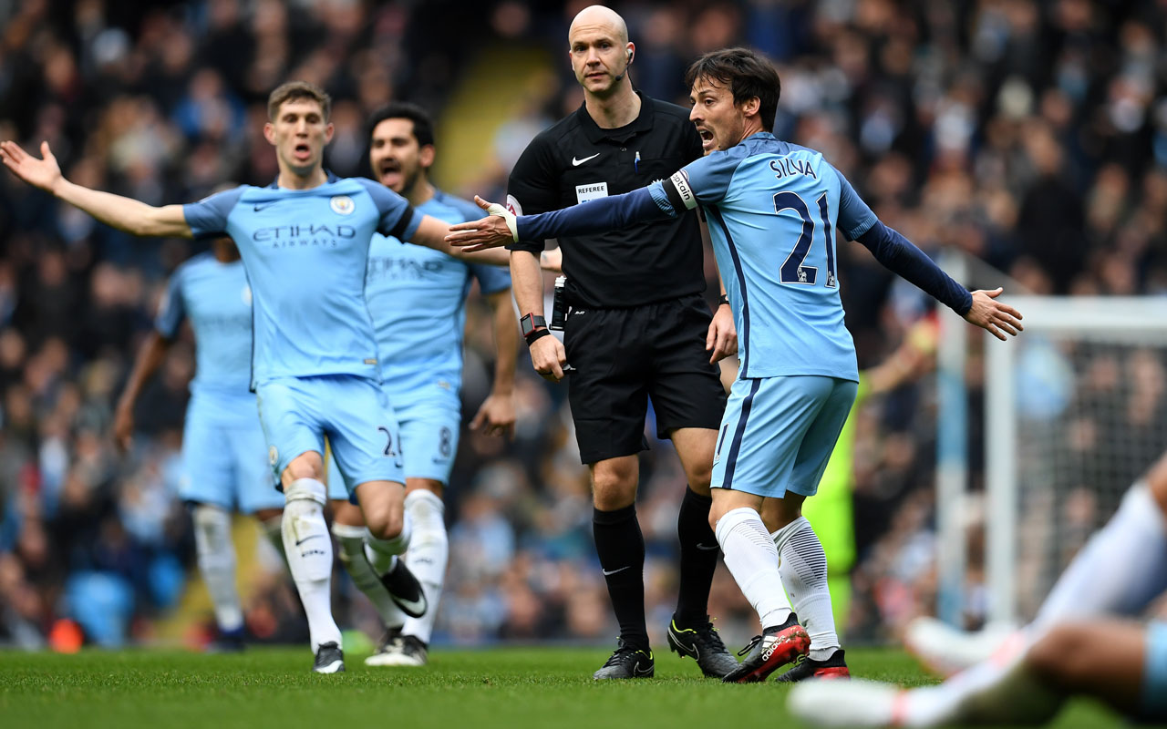 Manchester City's Spanish midfielder David Silva (R) and Manchester City's English defender John Stones (L) appeal to referee Anthony Taylor after Chelsea's Brazilian defender David Luiz (unseen) challenged Manchester City's Argentinian striker Sergio Aguero, during the English Premier League football match between Manchester City and Chelsea at the Etihad Stadium in Manchester, north west England, on December 3, 2016. No foul was given. / AFP PHOTO / Paul ELLIS /