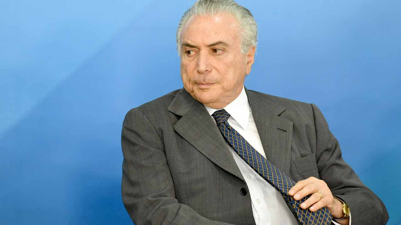 Brazilian President Michel Temer gestures during the launch of the Public Transport Fleet Renewal Program at Planalto Palace in Brasilia, on December 13, 2016. Temer celebrated the approval by the National Congress of the constitutional amendment that establishes the limit of expenses for the government in the annual budget.  EVARISTO SA / AFP