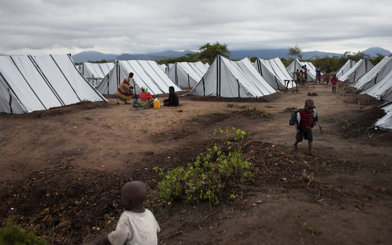Internally displaced Mozambican children and people, who fled clashes between the Mozambican Army and Mozambican National Resistance forces (RENAMO), stand in an internal displacement camp on December 12, 2016 in Vanduzi in the Manica Province. This year has seen a sharp escalation in violence, and more than 15,000 people have been forced to flee to government-run camps, relatives' homes or across the border to Malawi and Zimbabwe. The clashes between longtime rivals, the Frelimo government and Renamo, an armed insurgent group and also an elected opposition party, have revived the spectre of Mozambique's civil war that ended more than 20 years ago. / AFP PHOTO / John WESSELS