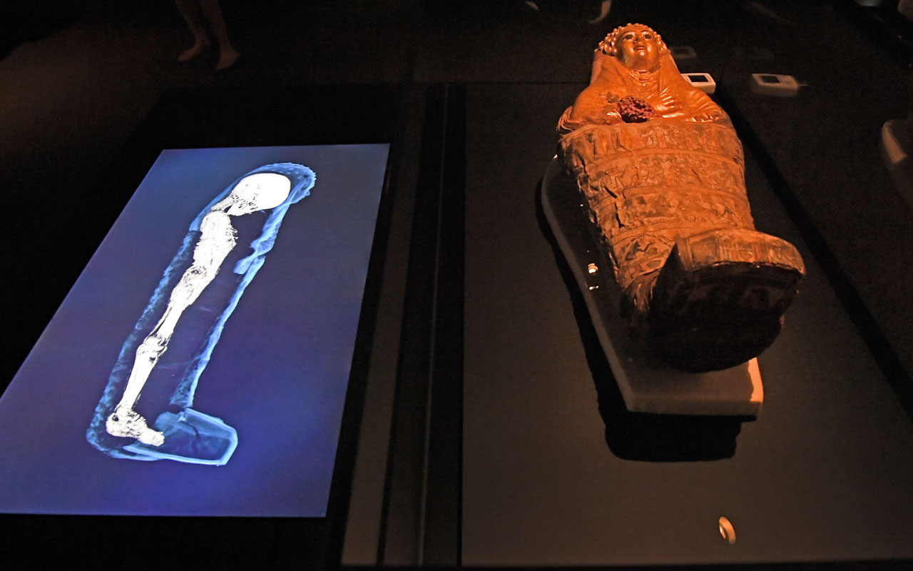 A three-dimensional image of a CT scan of an Egyptian mummy is projected beside a sarcophagus as the hidden secrets of Egyptian mummies up to 3,000 years old have been virtually unwrapped and reconstructed for the first time using cutting-edge scanning technology in a joint British-Australian exhibition in Sydney on December 8, 2016. Three-dimensional images of six mummies aged between 900BC and 140-180AD from ancient Egypt, which have been held at the British Museum but never physically unwrapped, give an insight into what it was like to live along the Nile river thousands of years ago. / AFP PHOTO / WILLIAM WEST