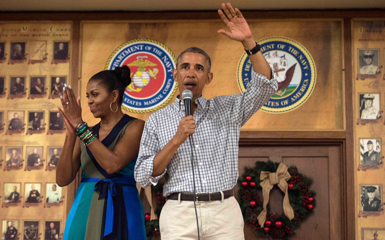 US President Barack Obama addresses troops with First Lady Michelle Obama at Marine Corps Base Hawaii in Kailua on December 25, 2016. / AFP PHOTO / NICHOLAS KAMM